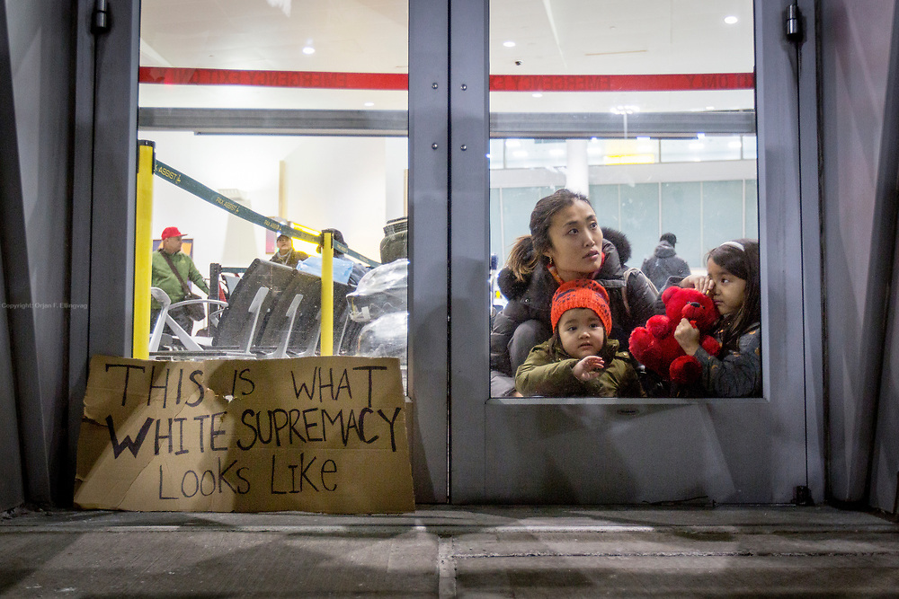 "A mother with two children looks at the protesters outside Terminal 4 at the JFK Airport in New York. A poster next to her says ""This is what white supremacy looks like"". The demonstrators partially shut down the terminal in protest of President Trump's immediate travel ban from seven predominately muslim countries."