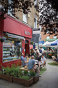 South Londoners enjoy al fresco cafe street life in Herne Hill station during a summer heatwave.