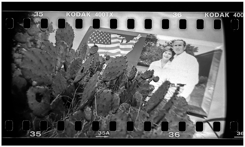 A billboard of U.S. President George W. Bush and first lady Laura Bush hangs over a cactus bush in Crawford, Texas, December 13, 2008. Bush moved to the small Texas town, population 705, in 1999 during his run for the presidency in 2000. The effect of the image was achieved by shooting 35mm black and white film in a medium format camera thereby exposing the entire negative including the sprocket holes of the film. REUTERS/Jim Young