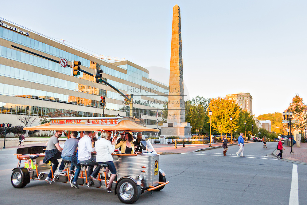 The Amazing Pub Cycle passes the Vance Monument in Pack Square Park in Asheville, North Carolina.