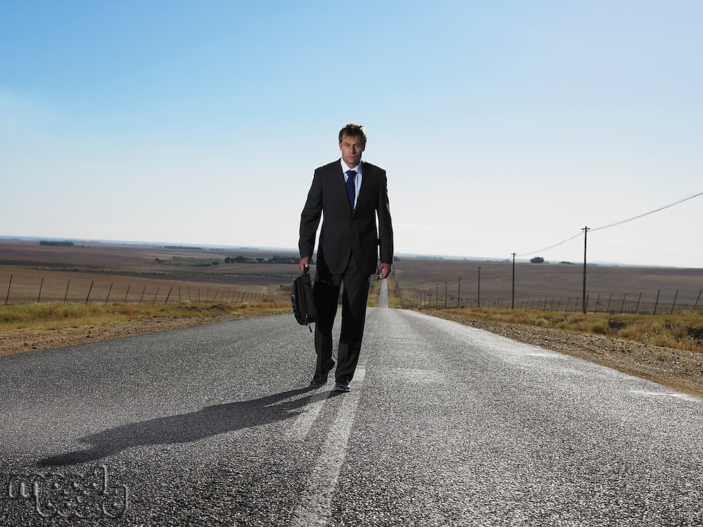 Businessman walking down road in isolated landscape