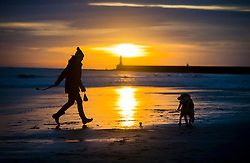 © Licensed to London News Pictures. 25/12/2015. Tynemouth, UK. A woman playing with her dog at sunrise on Christmas day on Longhands beach in Tynemouth, north east England. Photo credit: Ben Cawthra/LNP