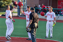 NORMAL, IL - April 08: Umpire Phil Pupillo watches as Derek Parola and Jack Butler congratulate John Rave on a 2 run homer during a college baseball game between the ISU Redbirds  and the Sacramento State Hornets on April 08 2019 at Duffy Bass Field in Normal, IL. (Photo by Alan Look)