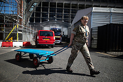 © Licensed to London News Pictures . 21/04/2020. Manchester, UK. MAJOR DEE wheels a trolley around the outside of the hospital . The National Health Service has built a 648 bed field hospital for the treatment of Covid-19 patients , at the historical railway station terminus which now forms the main hall of the Manchester Central Convention Centre . The facility is treating patients from across the North West of England , providing them with general medical care and oxygen therapy after discharge from Intensive Care Units . Photo credit : Joel Goodman/LNP