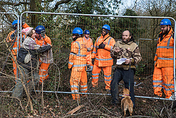 Harefield, UK. 7 February, 2020. Activists lean on Heras fencing being erected by HS2 engineers to surround three environmental activists from Extinction Rebellion who have climbed a veteran oak tree close to the Harvil Road wildlife protection camp in order to try to protect it from felling. HS2 are expected to try to fell large numbers of mature trees in the immediate vicinity over the weekend even though the high-speed rail link is still awaiting Boris Johnson's approval.