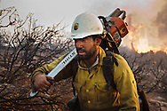 Daniel Diaz, a sawyer in the Kern Valley Hotshots, ends the day carrying his 25 lb (12 kg) chainsaw up a hill after clearing heavy brush around a spot fire at the La Brea Fire.