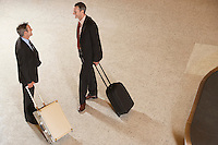 Two business men standing with suitcases by luggage carousel in airport