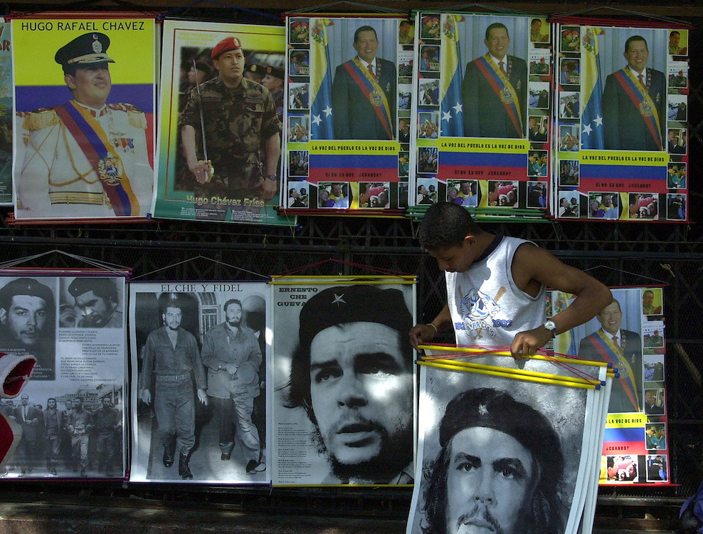 A vendor sets up poster of Venezuelan President Hugo Chavez, Fidel Castro and Che Guevar, Dec. 20, 2002, outside the Venezuelan Senate building in dowetown Caracas. The  country is in the midst of a crippling 18 day strike that has pitted supports and opponents of Chavez against each other.