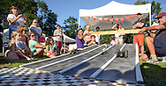 Participants watch as cars made from zucchini speed down the track during the zucchini races at Lower Makefield Farmer Market Thursday August 13, 2015 in Lower Makefield, Pennsylvania. Participants can create race cars out of zucchinis by poking holes into the veggies to put in axles made out of items like toothpicks or wooden skewers, the organizers said. Wheels, made out of any type of material, can be attached to the axles. No motor cars or remote controls are allowed, according to organizers. (Photo by William Thomas Cain)