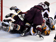 24 FEB. 2010 -- ST. LOUIS -- DeSmet's hockey team mobs David Goodwin (9, face visible) after Goodwin scoredthe game-winning goal in overtime to beat CBC 5-4 for the Mid States Club Hockey Association Challenge Cup at the Scottrade Center in St. Louis Wednesday, Feb. 24, 2010.  Photo (c) copyright by Sid Hastings.