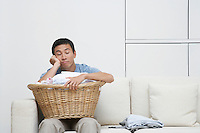 Tired Man resting head in hand on full Laundry basket sitting on Sofa