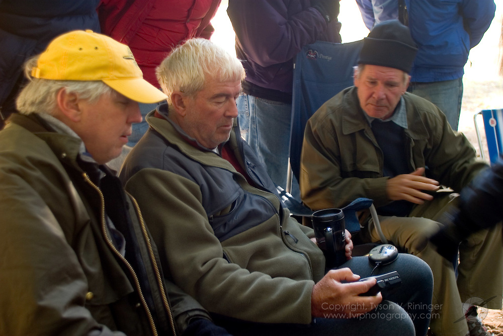 Harrison Ford and other campers look on as Dr. Richard 'Doc' Sugden demostrates the new, at the time, Garmin 396 GPS unit during a backcountry flying expedition in Moose Creek, Idaho.
