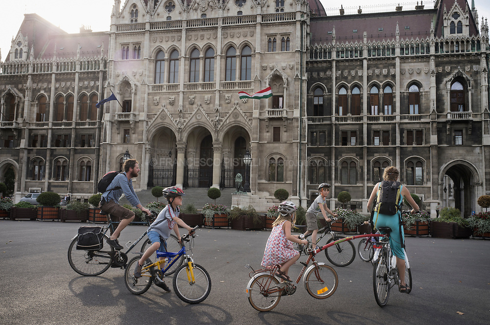 Hungary 2011. Budapest. Parliament building. A family by bike. Budapest is one of the most cyclable capitals in Europe.