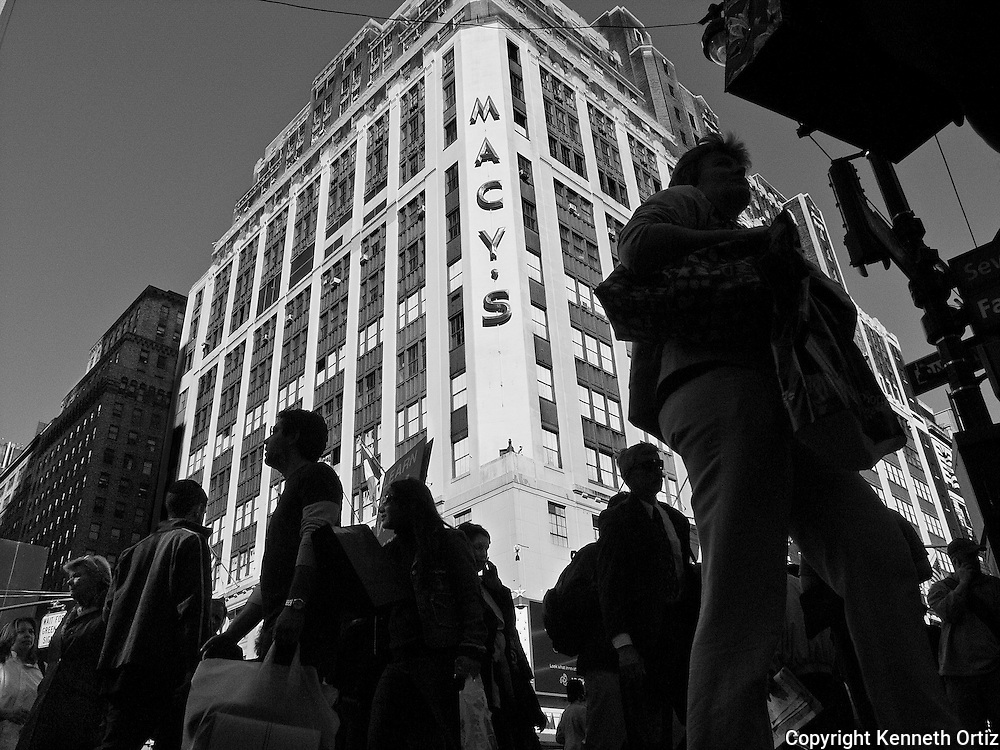 Shoppers crisscross down 7th Avenue past Macy's.