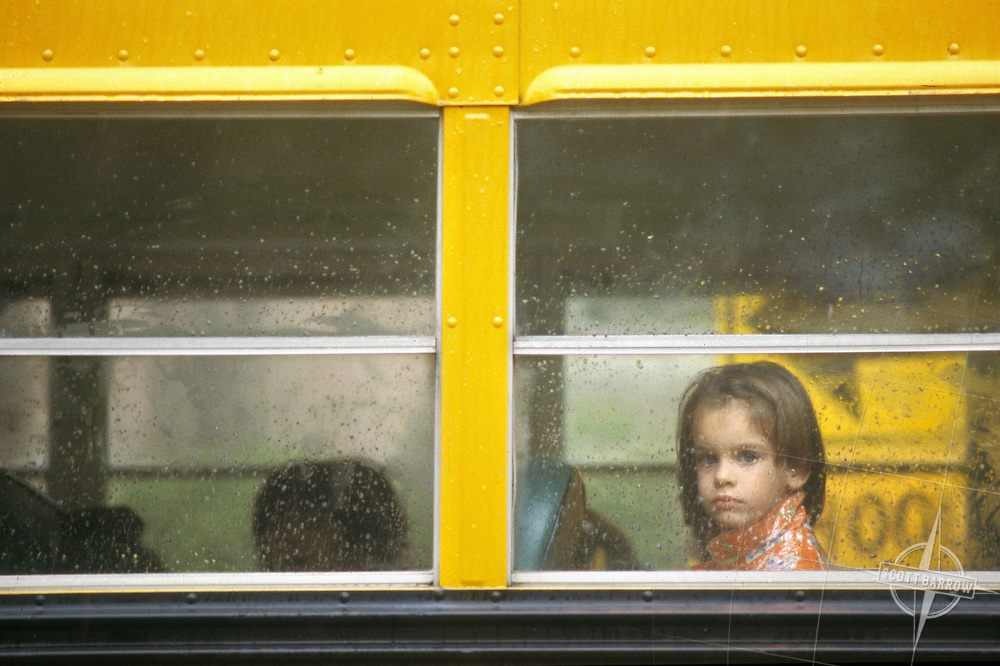 Young girl in school bus window.