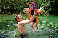 A grandfather plays with his grandson in the swimming hole at the popular Babinda Boulders.