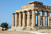 Temple E or Temple of Hera, built 460-450 BC, on the East Hill of the ancient ruined Greek city of Selinunte, Sicily, Italy. The peristyle consists of 6 x 15 Doric columns with several staircases and traces of stucco and friezes. It was rebuilt 1956-59. Selinunte was founded in 628 BC and was an important Greek colony, home to up to 100,000 people at its peak and abandoned in 250 BC. The city consists of an acropolis housing 2 main streets and 5 temples, 3 other hills with housing and temples and 2 necropoleis. Picture by Manuel Cohen