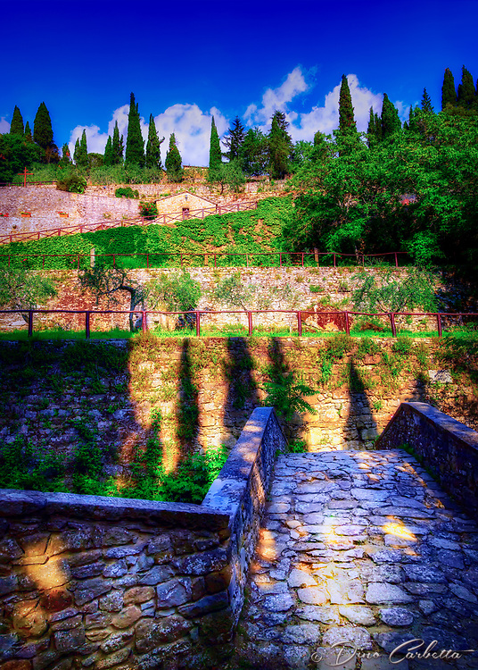"""""""Ancient bridge to the Convent of cells - founded by San Francesco in Cortona""""...<br /> <br /> Known as Le Celle, this Franciscan hermitage is just five miles from Cortona at the foot of Mount Sant' Egidio. In 1211, St. Francis along with a few of his followers built the first nine cells of the hermitage, and it has taken the name of Le Celle ever since. Inside the tiny cell belonging to St. Francis is a tiny window, the bed on which he slept, his desk, and a painting of the Madonna and Child where he prayed. The Hermitage invokes a peaceful atmosphere of spirituality and solitude, yet it is vibrant with religious life. Currently, the hermitage is inhabited by seven friars who continue to practice the teachings of St. Francis. I found Le Celle to be one of the pleasant surprises in and around Cortona. The tiny cells built into the side of the mountain with a stream descending along the structural edge, creates a surreal and picturesque vision of Saint Francis' image of God and nature. The convent is able to offer lodgings to those contemplating a vocational life. Just inside one of the doors to Le Celle, I noticed the sunlight shining delicately through the transom window gently illuminating the old wooden door and cross. This image epitomizes all the simplicities in which Saint Francis preached and lived. It represents his spartan structure with the rough textured concrete walls, antique faded wooden door, the green trees in nature which he loved, and the mystic evening sun softening the aging appearance, and revealing his simple life of prayer and personal austerity."""