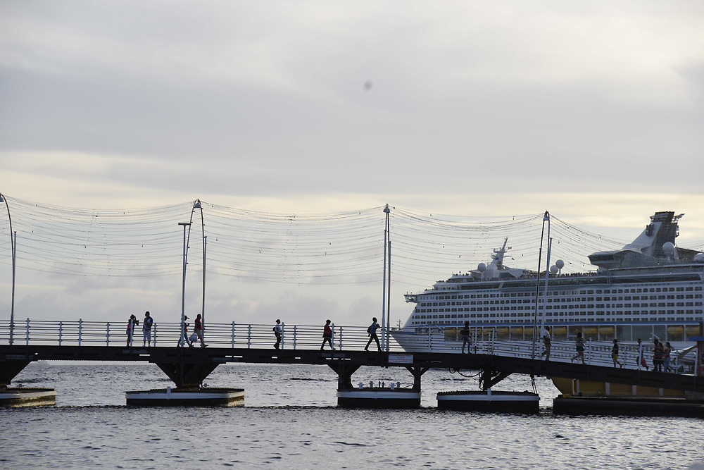 WILLEMSTAD, CURACAO - DECEMBER 12, 2014:  A cruise ship heads out to see as people locals and tourists head across the Queen Emma Bridge, a walkable pontoon bridge, that goes across the Santa Anna Bay. (photo by Melissa Lyttle)