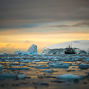 An Antarctic cruise ship in the distance past the brash ice and small icebergs, as the setting sun casts a golden glow on the horizon.