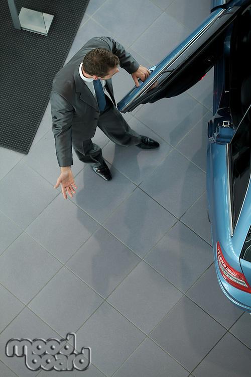 Salesperson opening door for customers at showroom