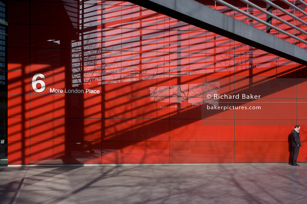 Diagonal shadows and the red theme of a modern office exterior at 6 More London, where a solitary man makes a call.