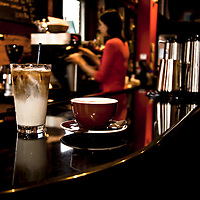An iced coffee or iced latte in a large glass next to a hot latte on a black countertop in a bar setting. People are in the background but are not distinguishable