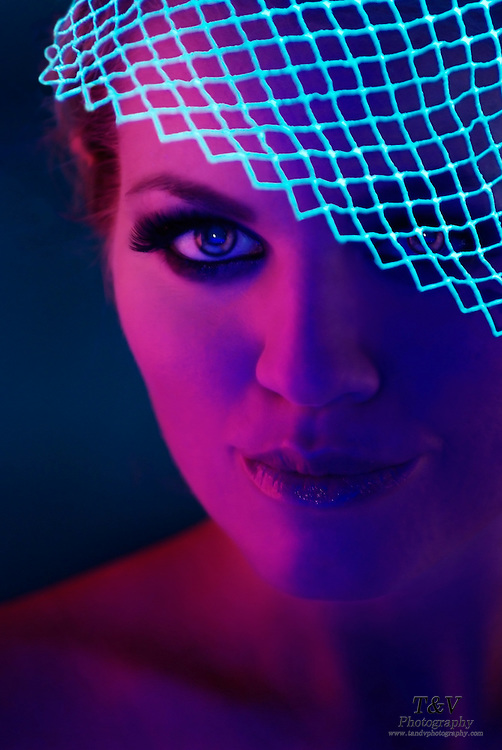 Portrait of a young woman with a veil covering part of her face.Black light