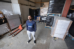 "© Licensed to London News Pictures. 07/05/2020. Salford, UK. Manager at Puro Medico SALAIMAAN MAJID (28) stands in the empty space in the warehouse from where the PPE was stacked up when it was stolen . £166,000 (one hundred and sixty six thousand pounds) worth of protective masks , which were destined for the NHS and care homes , have been stolen from a warehouse overnight (6th-7th May 2020) in what Greater Manchester Police are describing as a "" targeted burglary "" . Thieves cut the shutters at the loading bay of Puro Medico - which specialises in importing PPE such as masks from China and hand sanitiser from Poland - and stole several pallets of stock , which was loaded on to vans over a two hour period . Photo credit: Joel Goodman/LNP"