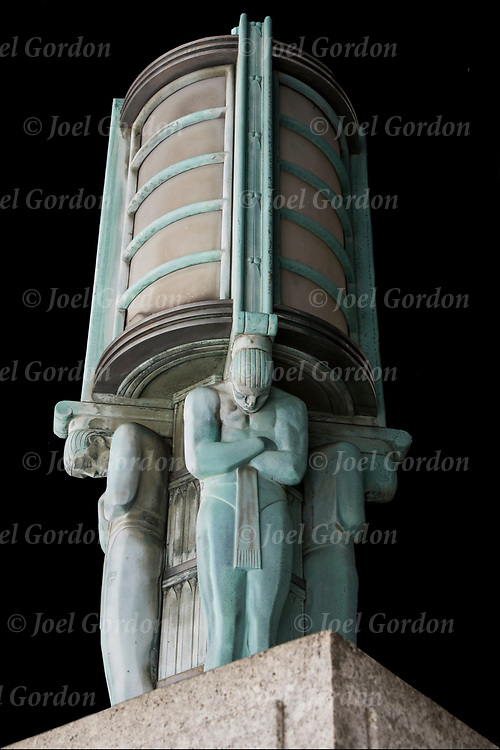 Art Deco light base with male figures holding up outdoor light fixture in front entrance of building on Centre Street in lower Manhattan.