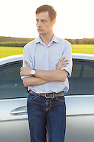 Young man looking away while standing by car at countryside