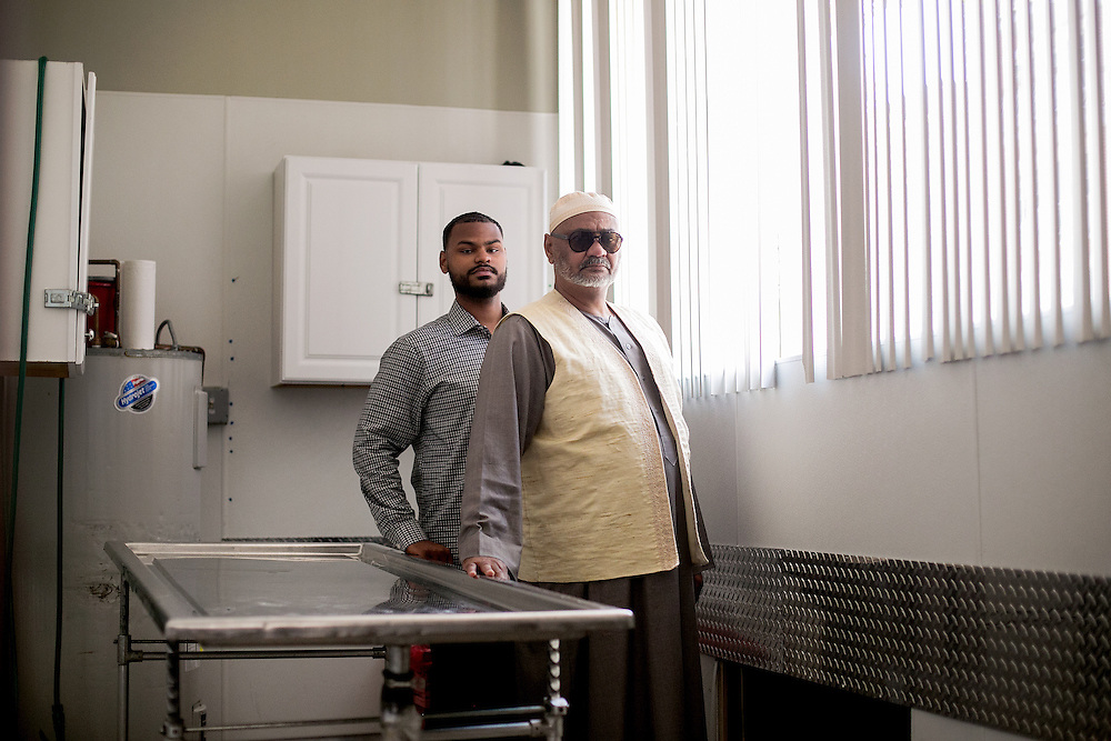 BROOKLYN, NY - JUNE 30, 2016: Funeral Director Awad Elmatbagi and his son Kareem (left) pose for a portrait inside the washroom where they prepare bodies at Islamic International Funeral Services in Sunset Park, Brooklyn, New York. CREDIT: Sam Hodgson for The New York Times.