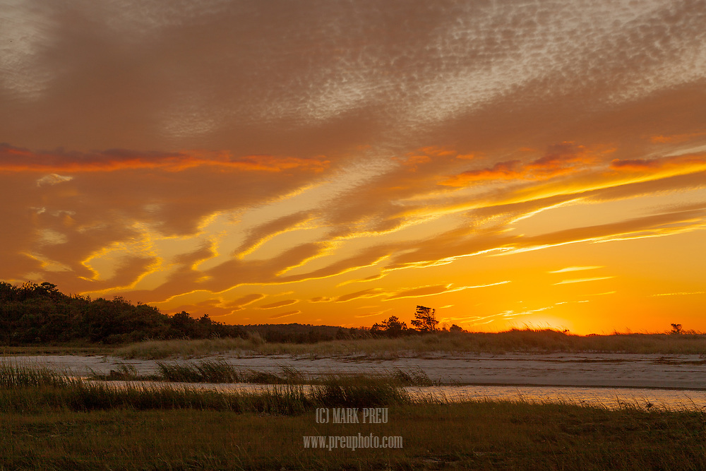 Yellow and orange clouds dominate the sunset sky at Paine's Creek Beach.