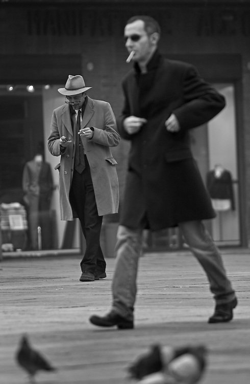 Two men walking on square in Bologna Italy.
