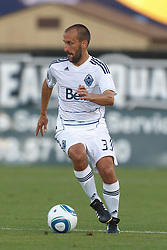 July 20, 2011; Santa Clara, CA, USA;  Vancouver Whitecaps midfielder Peter Vagenas (33) dribbles the ball against the San Jose Earthquakes during the first half at Buck Shaw Stadium.
