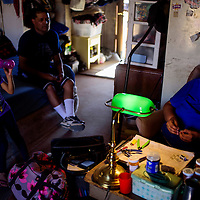 Emily Dodson, right, does beadwork by lamplight with Ray Johnson and De'lylah Tsosie at their home near White Mesa on the former Bennett Freeze Wednesday. Dodson's home and others that received infrastructure like electricity and plumbing when the freeze was lifted in 2009 are eligible for reconstruction.