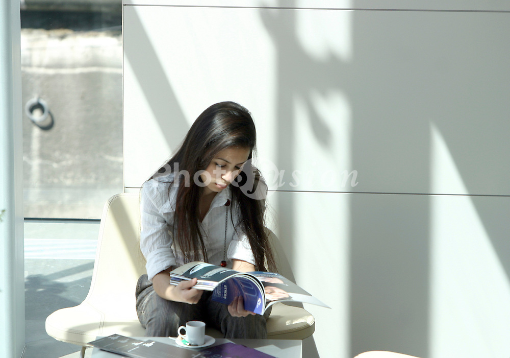 Young woman reading magazine and drinking coffee in cafe UK