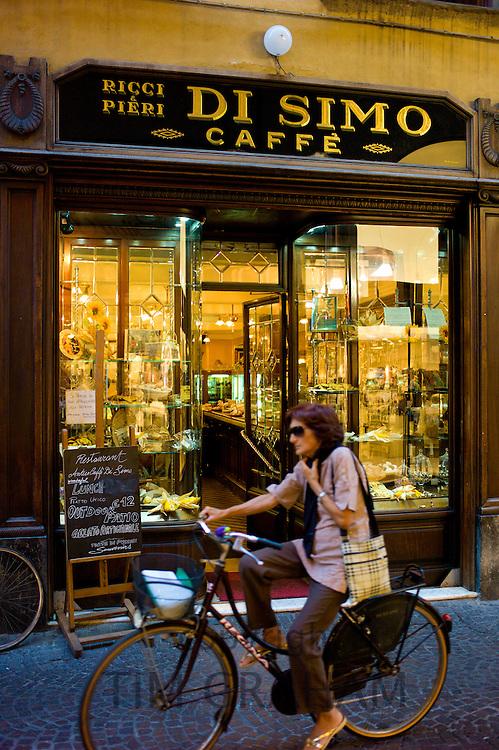 Cyclist passing Di Simo Caffe, Ricci and Pieri, in Via Fillungo,  Lucca, Italy