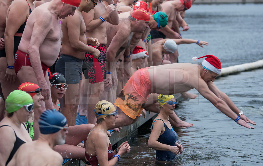 © Licensed to London News Pictures. 25/12/2017. London, UK. Competitors dive in at the start of the race as members of the Serpentine Swimming Club brave the cold waters at the Serpentine Lake in Hyde Park, London to compete for the traditional Peter Pan Cup on Christmas Day, December 25, 2017. Photo credit: Ben Cawthra/LNP
