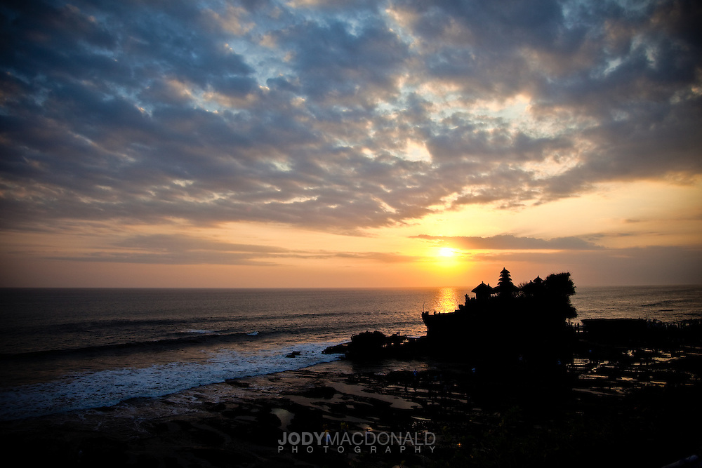 Sunset and a clouded sky provide beautiful relief over a temple built at the ocean's edge in Bali, Indonesia.  Waves crash on the shore and reef, giving pleasant acoustics to a sublime scene.