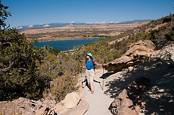 USA, Utah, woman hiking at Escalante at Escalante Petrified Forest State Park to enjoy the petrified wood, views of the Grand  Staircase and Colorado Plateau, and local vegetation such as pinon pine and Utah juniper. Model Release MR.