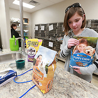 "Gabi Clayton, 12, of Mantachie sets out a couple of bags of puupy food at the Tupelo Lee Humane Society that she received as birthday gifts with the sole purpose of donating the items to the shelter. Clayton did this two years for the shleter in Fulton but she wanted to help the Tupelo shelter because as she says, ""Animals make me happy""."