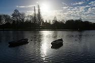 Nederland, Den Bosch, 20141210.<br /> De zon staat laag boven de horizon en schint over twee eenzame roeibotjes op het water. tegenlicht <br /> Het park langs de Schanswetering, wiel bij Fort Orthen<br /> <br /> Netherlands, Den Bosch, 20141210<br /> sun low on the horizon shining over two lone backlit rowing boats in the water.