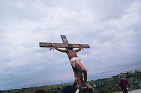 """MATERA, ITALY -6 OCTOBER 2019:  Yvan Sagnet (34), a political activist and former exploited tomato farmer, is seen here performing Jesus Christ in the scene  of the crucifixion in """"The New Gospel"""", a film by Swiss theatre director Milo Rau, in Matera, Italy, on October 6th 2019.<br /> <br /> Theatre Director Milo Rau filmed the Passion of the Christ  under the title """"The New Gospel"""" with a cast of refugees, activists and former actors from Pasolini and Mel Gibson's films.<br /> <br /> The role of Jesus is performed by Yvan Sagnet, a Political activist born in Cameroon and who worked on a tomato farm when in 2011 he revolted against the system of exploitation and led the first farm workers' strike in southern Italy. In a series of public shoots in the European Capital of Culture Matera, Jesus will proclaimed the Word of God, was crucified (October 6th 2019) and finally rose from the dead in Rome, the capital of Catholic Christianity and seat of one of the most xenophobic governments in Europe (October 10th 2019).<br />  <br /> Parallel to the film, the humanistic message of the New Testament was transformed into the present: at the beginning of September, the campaign """"Rivolta della Dignità"""" (Revolt of Dignity), which demanded fair working and living conditions     for refugees, global freedom of travel and civil rights for all, started with a march from the southern Italian refugee camps. """"It's about putting Jesus on his feet,"""" director Milo Rau said. Led by Jesus actor Yvan Sagnet, the campaign fights for the rights of migrants who came to Europe via the Mediterranean to be enslaved by the Mafia in the tomato fields of southern Italy and to live in ghettos under inhumane conditions. The campaign and the film thus create a """"New Gospel"""" for the 21st century, a manifesto of solidarity with the poorest, a revolt for a more just and humane world."""