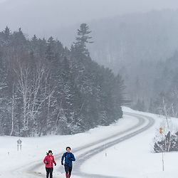A man and woman running on NH 16 in New Hampshire's White Mountains on a snowy winter day.