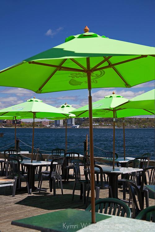 North America, Canada, Nova Scotia, Halifax. Outdoor tables and umbrellas on the Halifax waterfront boardwalk.