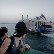 People watching the view from a ferry. Sydney Bay during sunset seen from a ferry. Sydney Opera House.