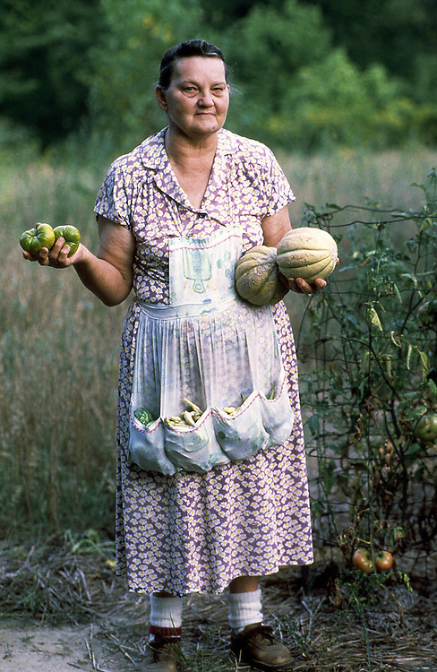 Indiana farm woman holds vegetables she has grown in her garden during a drought.