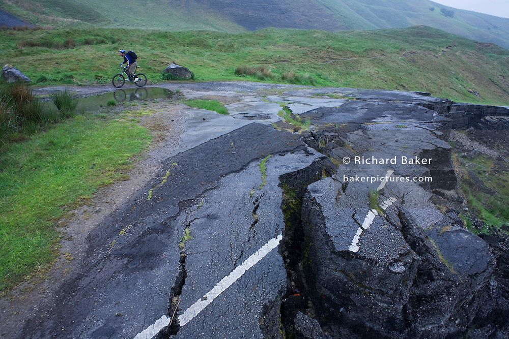 Cyclists struggle uphill near landslide road beneath Mam Tor in the in the Derbyshire Peak District National Park.