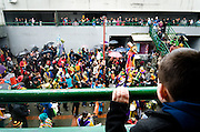 A child watches the carnival parade as it passes through a courtyard. He is possibly forbidden to join
